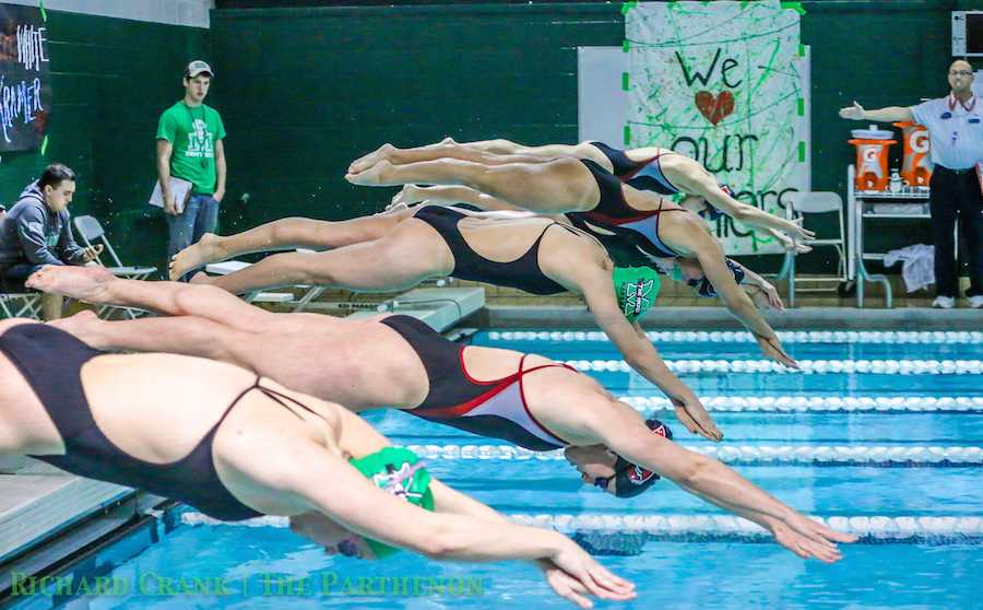 Members of Marshall University's swimming and diving team dive into the pool during a match against Western Kentucky University last season.