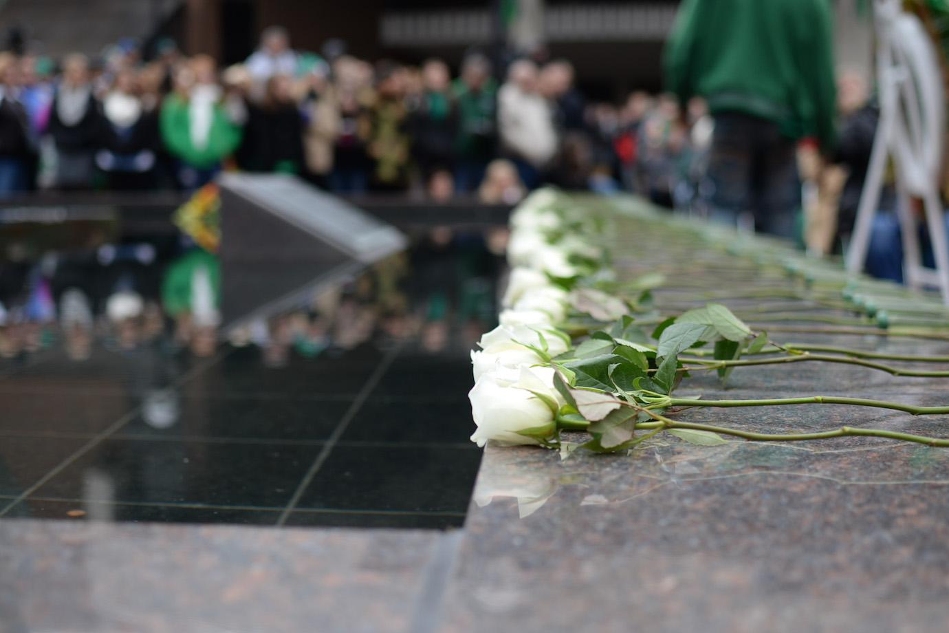 Members of the community and Marshall football players lay roses during the 44th annual Memorial Fountain Ceremony in commemoration of the 75 lives lost on the 1970.