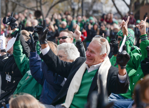 """Members of the Marshall University community at the Memorial Fountain Ceremony participate in Rev. Steve Harvey's """"Live it, Love it, Loyal to it,"""" a team tradition, Friday on the Memorial Student Center plaza."""