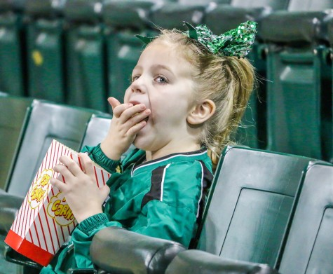 A young fan chows down on some popcorn as the Herd women take on Florida International University Thursday in the Cam Henderson Center.
