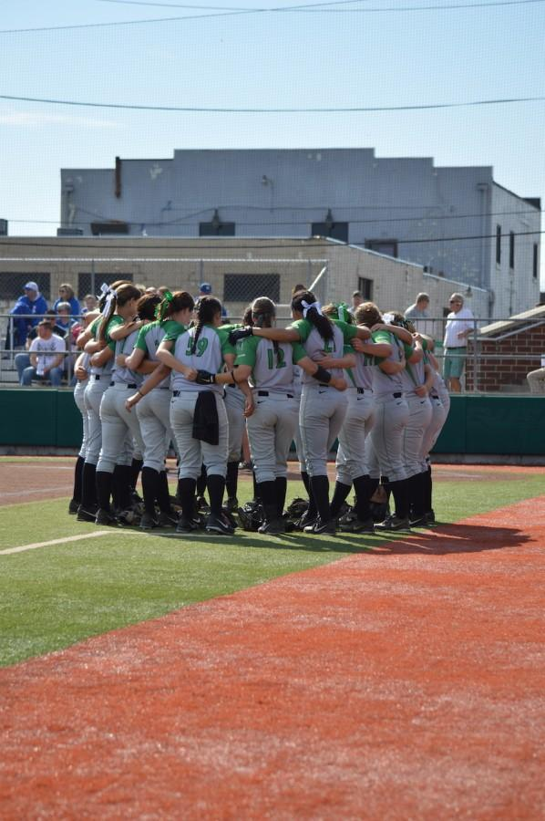 Members of the Thundering Herd softball team gather for a team meeting before its game with the University of Kentucky, March 11, 2014, at Dot Hicks Field.