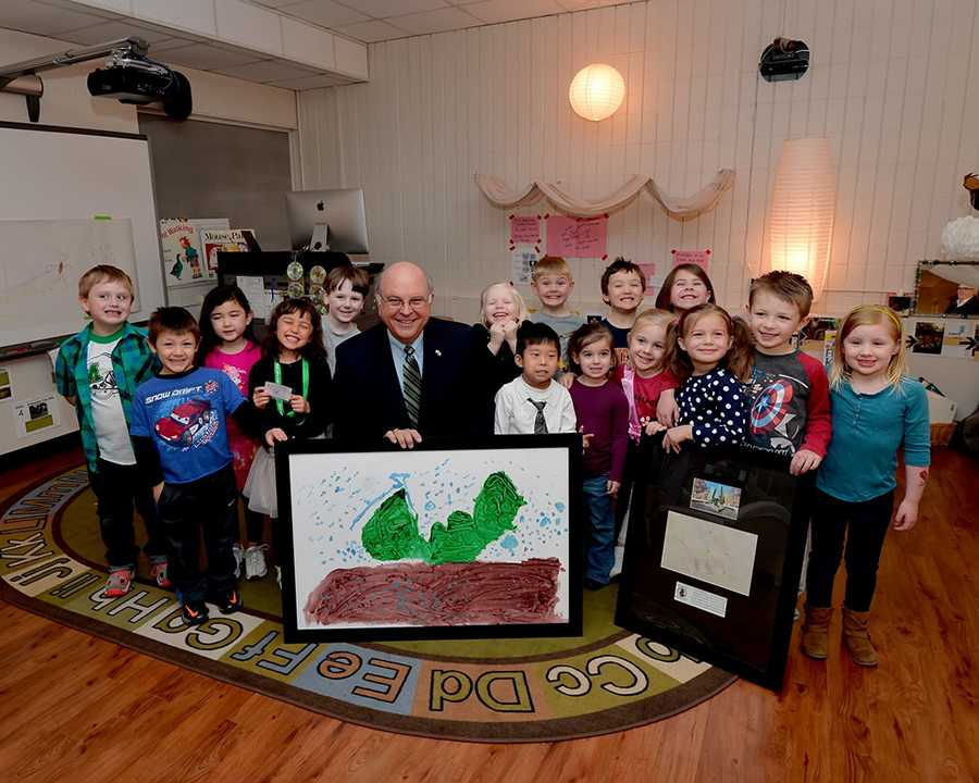 Interim President Gary White and the children pose with a picture the children drew of the Memorial Student Center fountain.