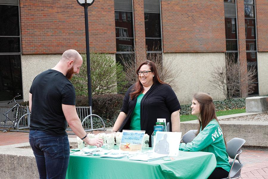 Alex Burgazzoli, graduate student in sociology, Crystal Stewart, program manager, information technology, and Alyssa Simon, student assistant, offer popcorn for students interested in finding out more about summer online classes offered through Marshall University.