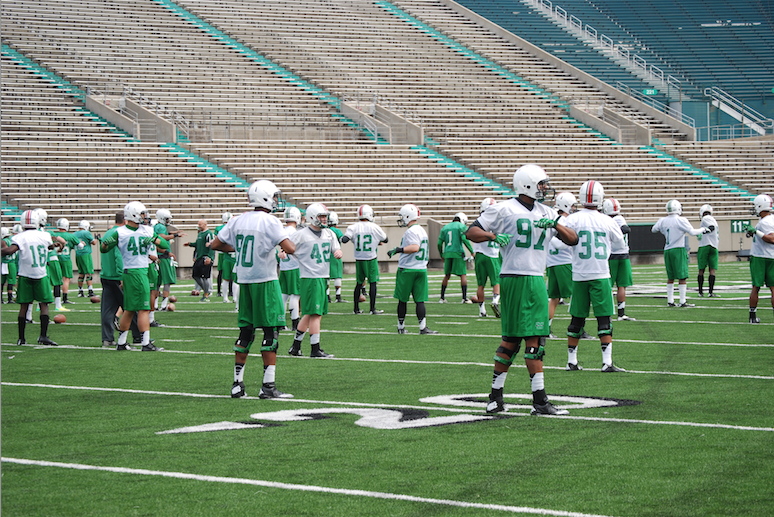 Players+warm+up+before+spring+football+practice+March+24+at+the+Joan+C.+Edwards+Stadium.