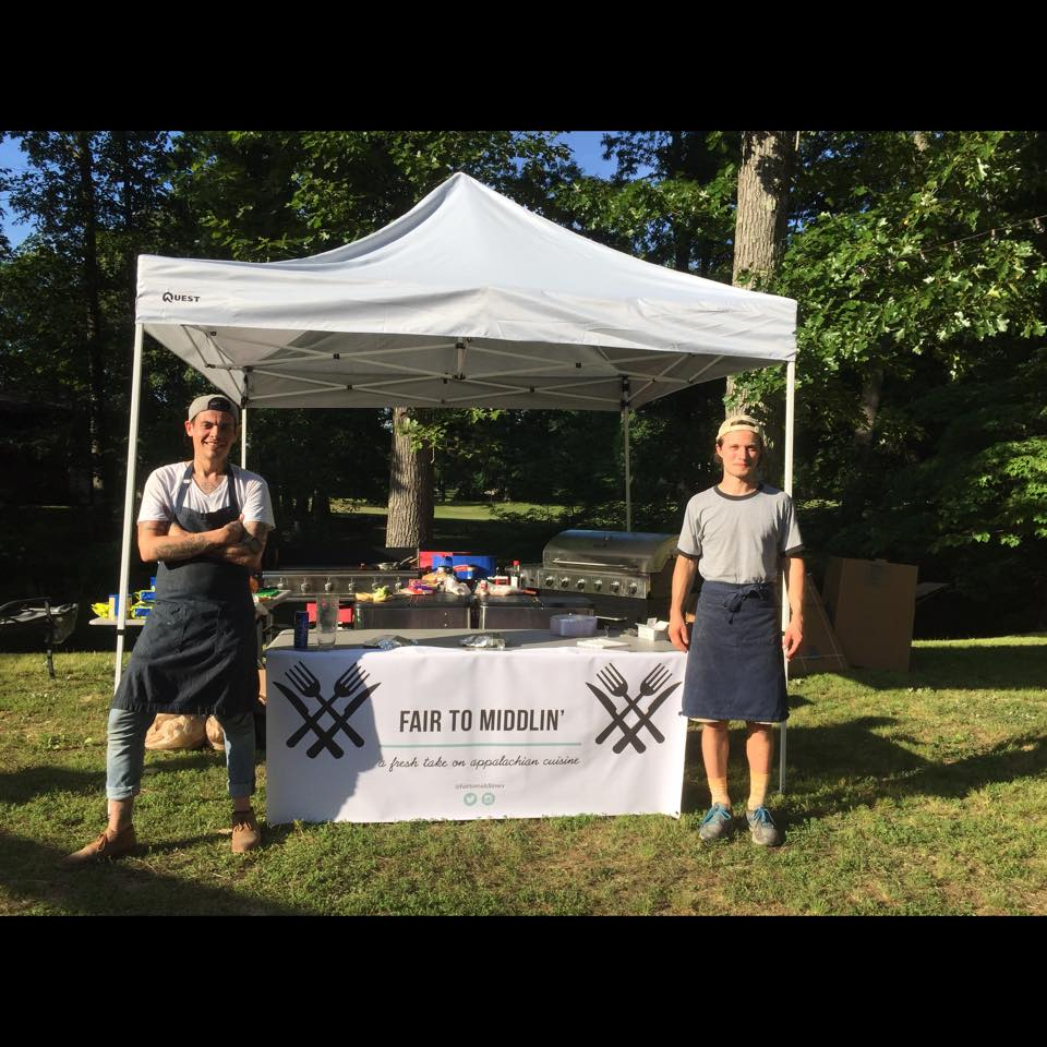 Owner Nicholas Taylor (left) stands beside his mobile kitchen at a recent engagement party the business catered.
