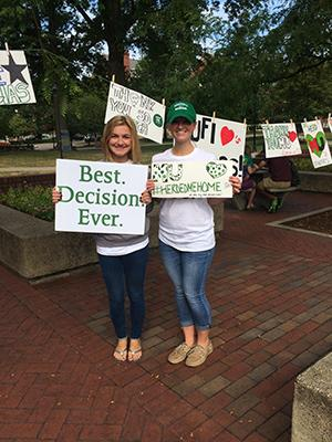 Liz (left) and Kristin (right) Bateman hold posters on Thank a Donor Day.