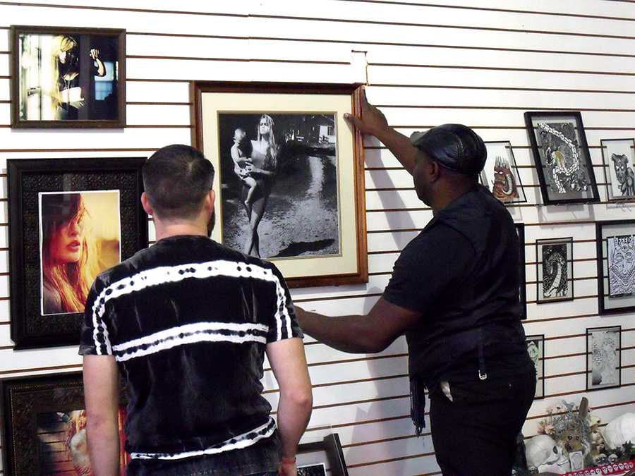 Keyamo Onage (right) , a photographer in the exhibit, hangs up his work with Joe Troubetaris (left) assisting. The art exhibit was curated by Two-Headed Dog Collective, a non-profit organization that creates temporary public safe spaces for the arts in Huntington.