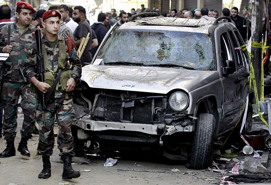 In this Friday, Nov. 13, 2015 file photo, Lebanese army soldiers stand guard near the damaged car of the family of Haidar Mustafa a three-year-old who was wounded in Thursday's twin suicide bombings, in Burj al-Barajneh, southern Beirut, Lebanon. Within hours of the Paris attacks last week that left 129 dead, outrage and sympathy flooded social media feeds and filled the airwaves. Commenting on the public outpouring of support and anger following the Paris attacks, Lebanese blogger Joey Ayoub accused the media and world leaders of caring less about deaths in Beirut in IS attacks than deaths in Paris at the hands of the same group. (AP Photo/Bilal Hussein, File)