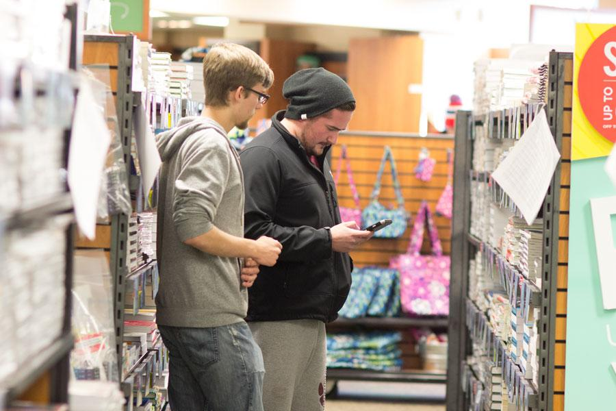 Jacob Thomas Howell, an employee, assists another student at the campus bookstore, January 19, 2016.