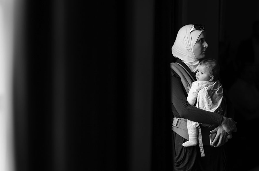 In this photo taken on Saturday, Dec. 12, 2015, Hiba Tinawi, from Syria, holds her 6-month-old daughter Judy during an event to welcome Syrian refugee families who have recently resettled in the city of Clarkston, Ga.