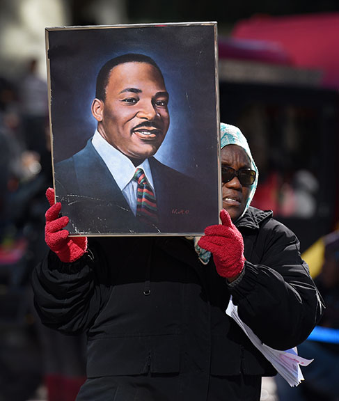 Kathy Williams walks the Martin Luther King, Jr. Day parade route with a portrait of the Civil Rights leader during the parade in Jacksonville, Fla., Monday, Jan. 18, 2016. Spectators lined  the streets of downtown  to watch the annual Martin Luther King, Jr. Day parade despite the chilly temperatures that started the day.  (Bob Self/The Florida Times-Union via AP)