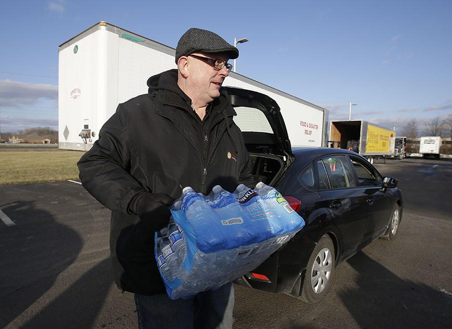 John Whitaker, executive director of Midwest Food Bank, carries a case of water that was donated, Wednesday, Jan. 27, 2016, in Indianapolis. All of the water that was collected will be sent to Flint, Mich., where drinking water has been contaminated by lead.