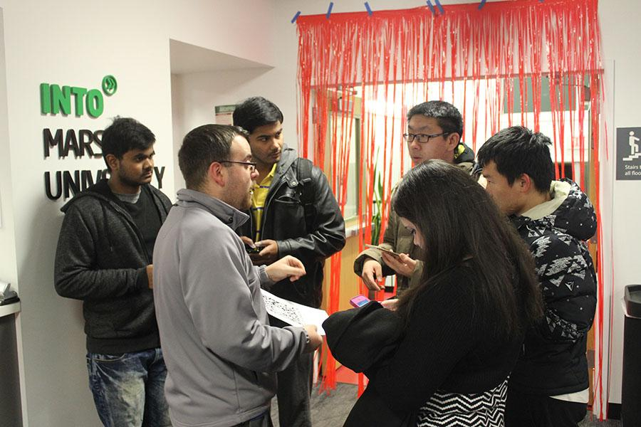 Kenny Jones, INTO Marshall student engagement coordinator, greets students at the INTO Chinese New Year celebration.