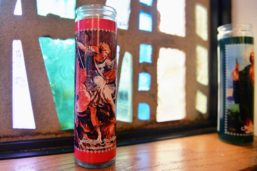A votive candle honoring Saint Michael the Archangel sits along the windowsill at the Newman Center.