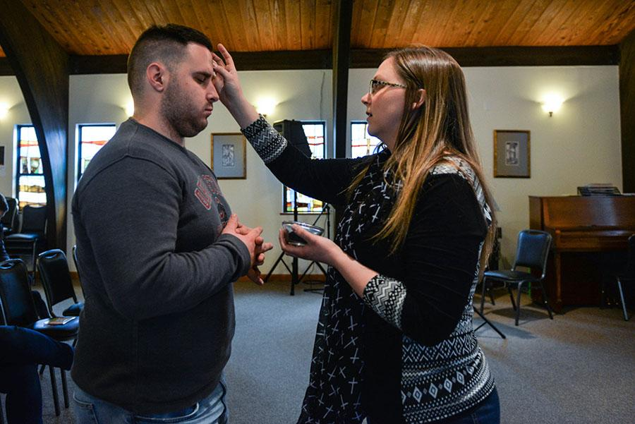 Traci Ferguson, Marshall University campus minister, traces ashes onto the foreheads of students for Ash Wednesday at the Catholic Newman Center.