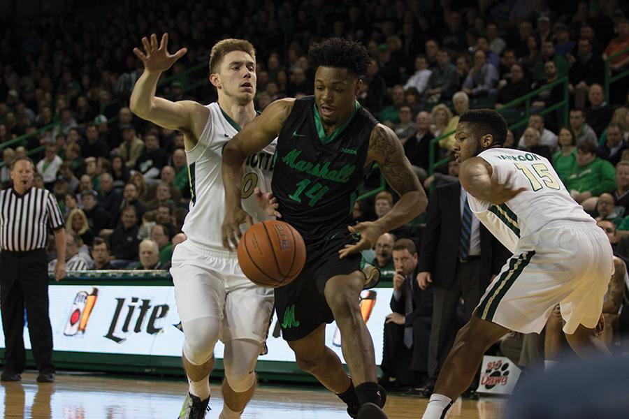 Marshall University freshman guard C J Burks goes after the ball Thursday against the University of North Carolina at Charlotte at the Cam Henderson Center.