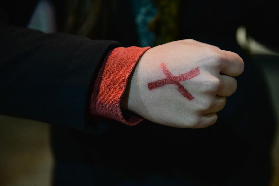"Marshall University students take turns standing outside the Memorial Student Center and sport red ""Xs"" on their hands in an effort to bring awareness to slavery and human trafficking on Thursday. The representatives  spent a total of 27 hours to represent the 27 million currently enslaved."