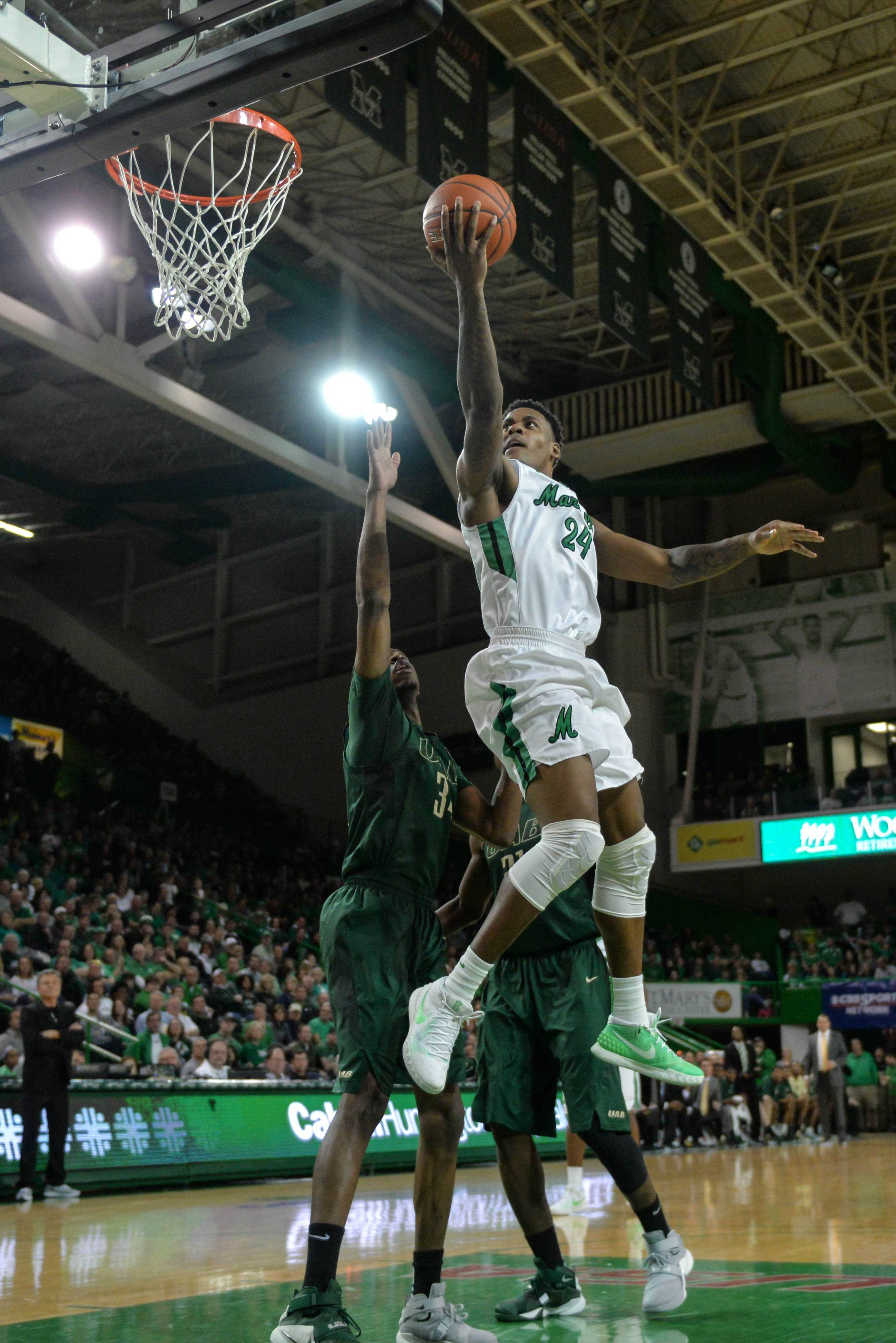 Marshall University senior forward James Kelly attacks the basket with two defenders on his heel Jan 30. against the University of Alabama at Birmingham at the Cam Henderson Center.