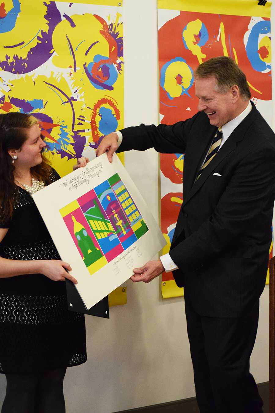 Junior graphic design student Brianna Jarvis presents her winning banners for the Winter 2016 category of the Huntington in Bloom banner contest to Mayor Steve Williams Tuesday at the Visual Arts Center.
