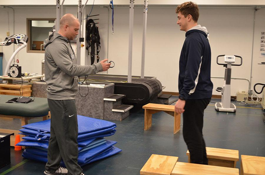 Hunter Perry, exercise science graduate student administers a step test to senior Eric Riley on Friday.