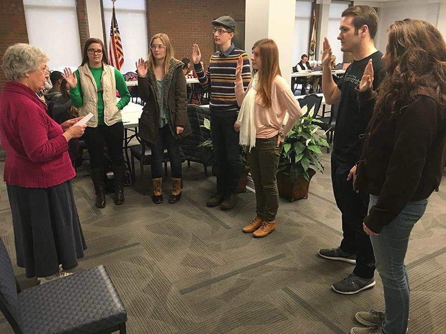 Carla Lapelle, interim dean of student affairs, swears in apprentices as senators at Student Government Association meeting.