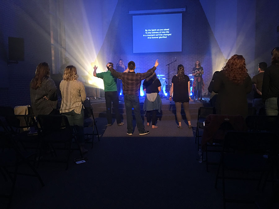 Students raise their hands in prayer and worship Monday night at a special Easter InsideOut service.