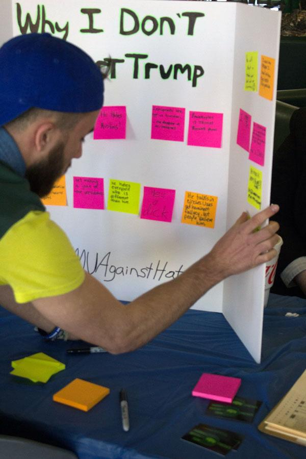 Students place sticky notes with why they don't support Donald Trump  at the Young Democrat's #MUAgainstHate table Tuesday in the Memorial Student Center lobby.