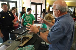 Larry Cartmill presents alongside his snake inside the Memorial Student Center during Earth Day, April 20, 2016.