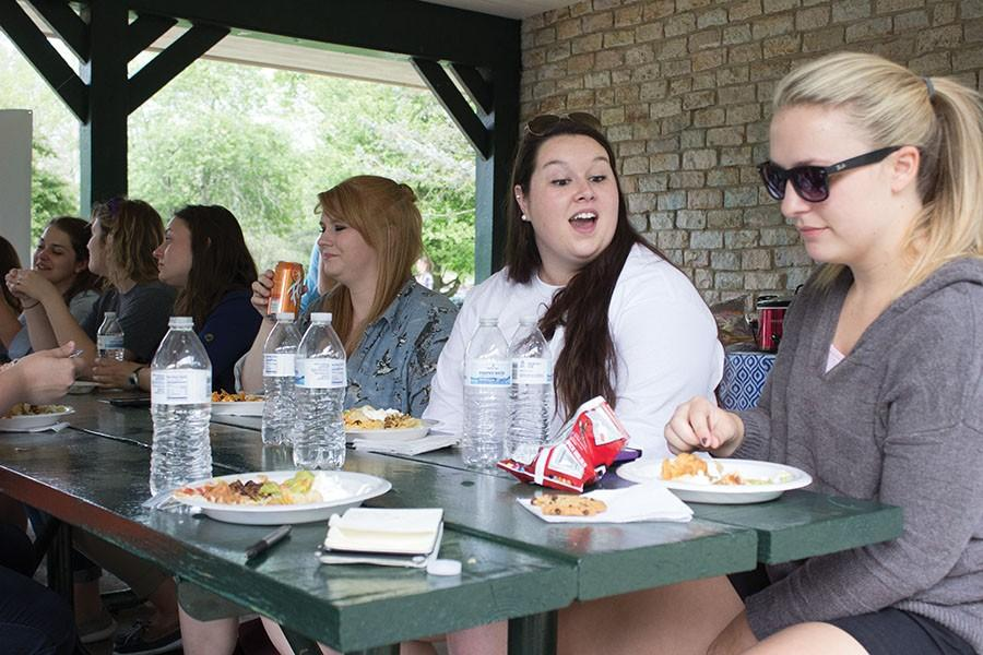 (From Right) Honors students Natalie Irwin, Ashley DeMoss, and Sarah McComas eat at the taco salad bar provided at the Honors College picnic in Ritter Park, April 21, 2016.