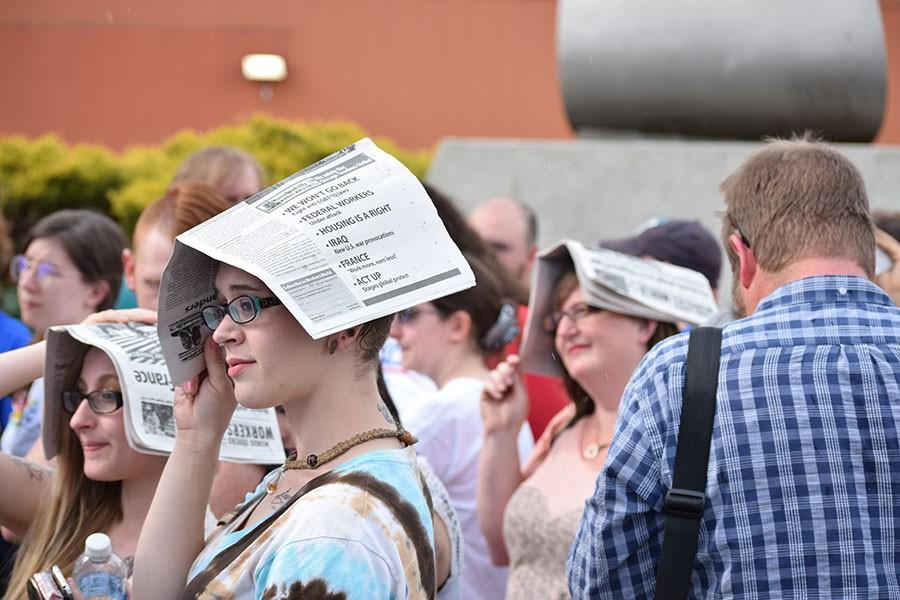 Kimberly McCartney, from Fairmont, shelters her head in a paper while standing outside the Big Sandy Superstore Arena for the Bernie Sanders rally, April 26, 2016.