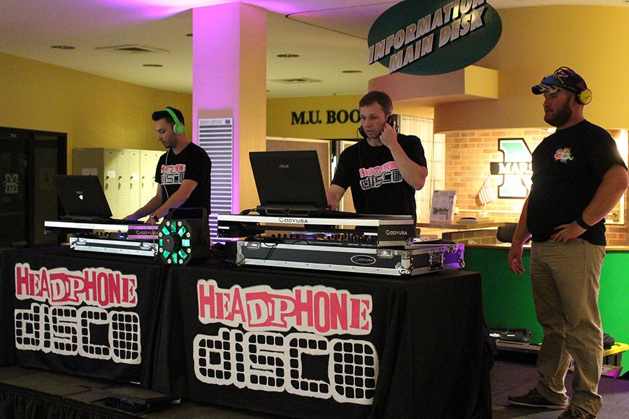 Headphone Disco's DJs Kory Scott (left) and Steven Crandall (middle) perform as Jacke Saunders of CAB (right)  takes in the scene Wednesday in the Memorial Student Center lobby.