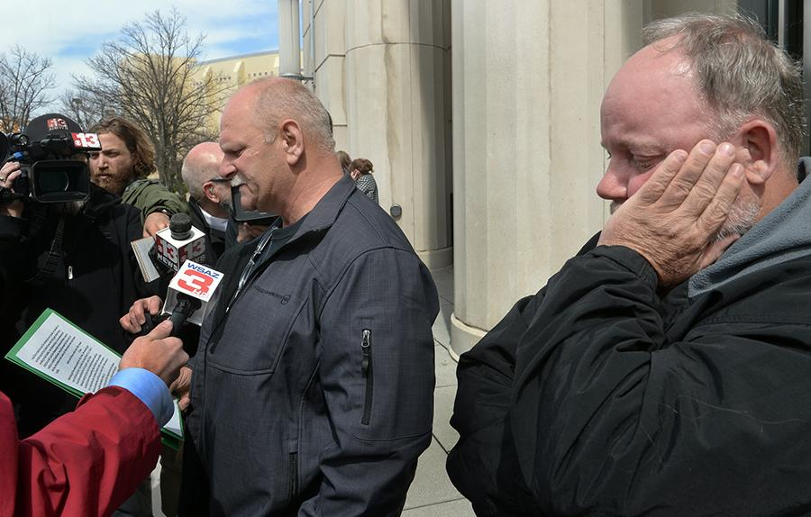 Clay Mullins, left, who lost his brother Rex Mullins in the Upper Big Branch explosion, reads the statement that he was not allowed to read during the sentencing of former Massey CEO Don Blankenship as Gary Quarles, right, who lost his son, takes in the emotion of the day Wednesday, April 6, 2016 in Charleston, W.Va. Blankenship was sentenced to a year in jail and a $250,000 fine for his role in the fatal 2010 blast.