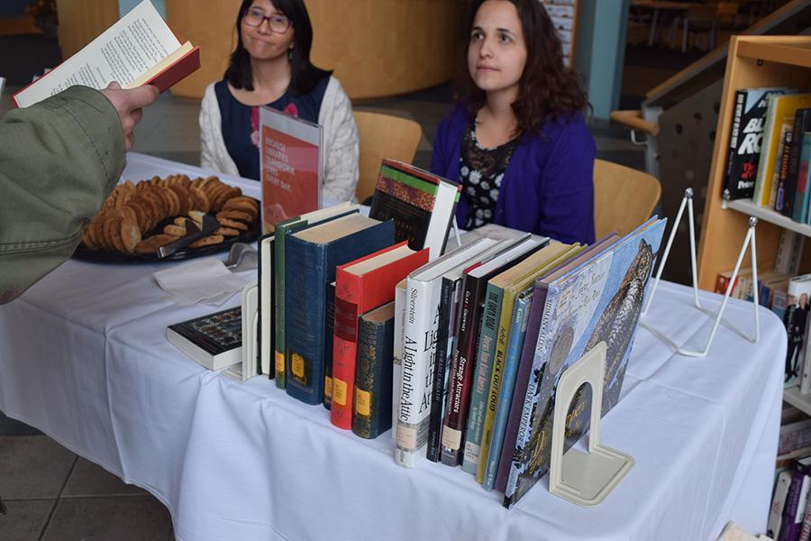 A student chooses a poem out of a book to read in exchange for a cookie Monday in Drinko Library for its Poem in Your Pocket table to celebrate National Library Week and National Poetry Month.