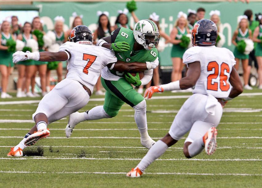 Marshall University's Emanuel Byrd splits the defense of Morgan State's Damare' Whitaker and Carl Garnes during Thundering Herd first half opening day football action Saturday at Joan C. Edwards Stadium in Huntington. Bob Wojcieszak/Parthenon