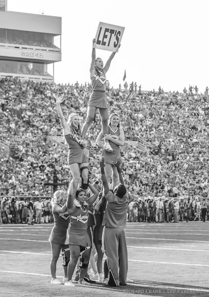 Marshall cheerleaders pepping up the crowd at a football game.