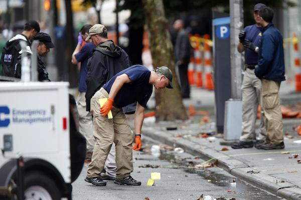 Evidence teams investigate at the scene of Saturday's explosion on West 23 Street in Manhattan's Chelsea neighborhood, Monday, Sept. 19, 2016, in New York. An Afghan immigrant wanted for questioning in the bombings that rocked a New York City neighborhood and a New Jersey shore town was captured Monday after being wounded in a gun battle with police. (AP Photo/Jason DeCrow)