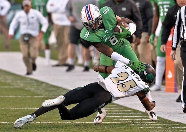 Marshall University slot receiver Josh Knight is tackled by Charlotte corner back Denzel Irvin during Thundering Herd football action Saturday afternoon at Joan C. Edwards Stadium in Huntington. Bob Wojcieszak/Parthenon