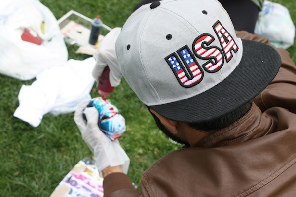 "Parthenon File Photo MSA member and Marshall graduate student Waleed Asif dons a ""USA"" hat as he dyes a shirt in the colors of the American flag on Buskirk Field in celebration of ""Hijab Day"" for Islam Awareness Week last semester."