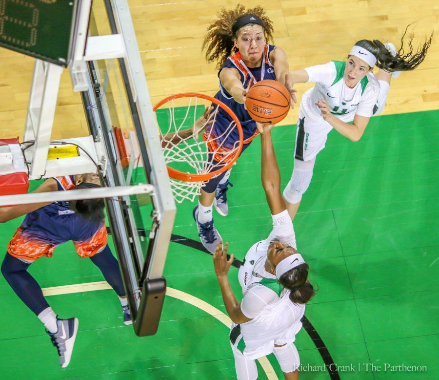 Marshall guard Taylor Porter (top) and Khadaijai Brooks (bottom) go up for a rebound against Morgan State on November 30. The Herd won 62-43.