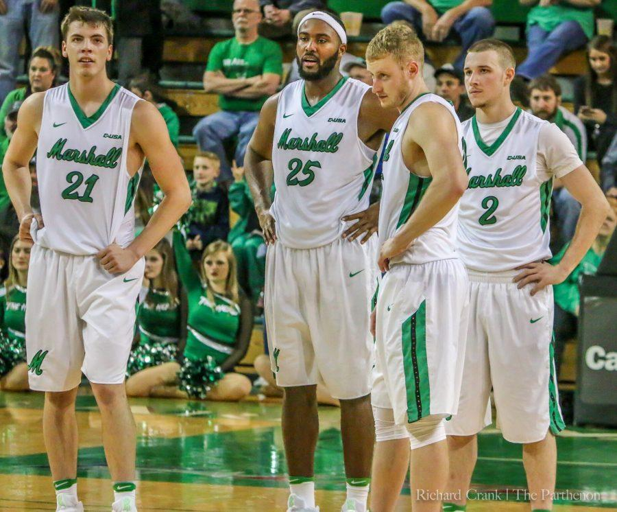 Marshall forwards Alex Nikolic (21), Ryan Taylor (25) and Austin Loop (35) and guard Stevie Browning (2) watch a free throw attempt late in the Herd's 98-88 win over rival Ohio University. Marshall is 5-0 at home this season.