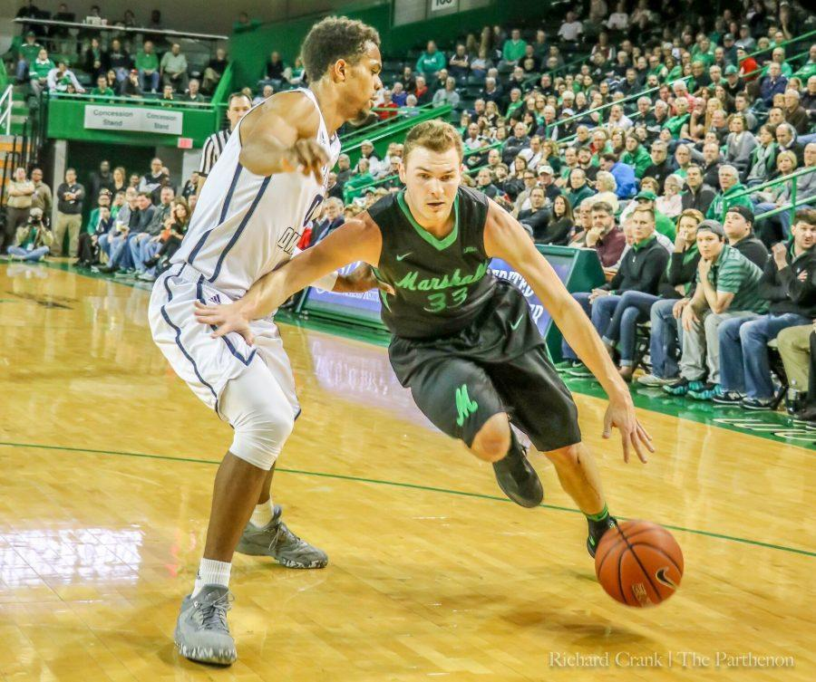 Marshall guard Jon Elmore (33) drives past a Rice defender earlier this season. Marshall ultimately fell to Rice, 89-88 on a last-second three-pointer.