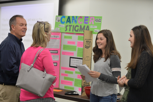 (From left) Randy and Caryn Short listen to Grayce Behnke and Deben Shoup elaborate on their project on cancer stigma during the disease fair Monday inside the Memorial Student Center.