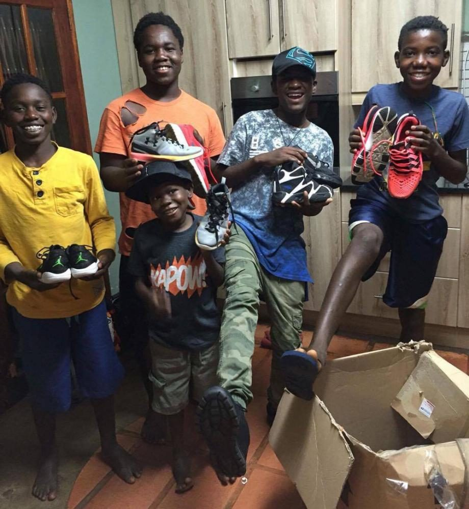 Boys from the Children's Village in Modjadjiskloof, in the Limpopo province of Africa holding up donations from Free Your Footwear.