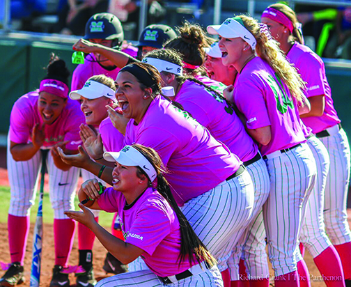 The Marshall University Softball team gathers around home plate celebrating a home run hit by sophomore Abigail Estrada Friday in the bottom of the second inning leading to a 4-2 win over FAU.