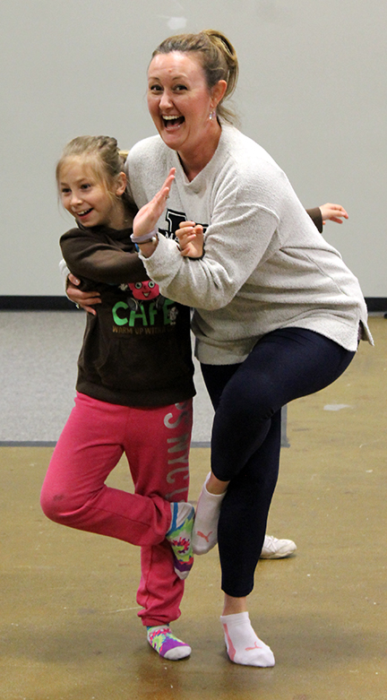 Big sister Carrie and little sister Hope pose while doing yoga at Girls' Day.
