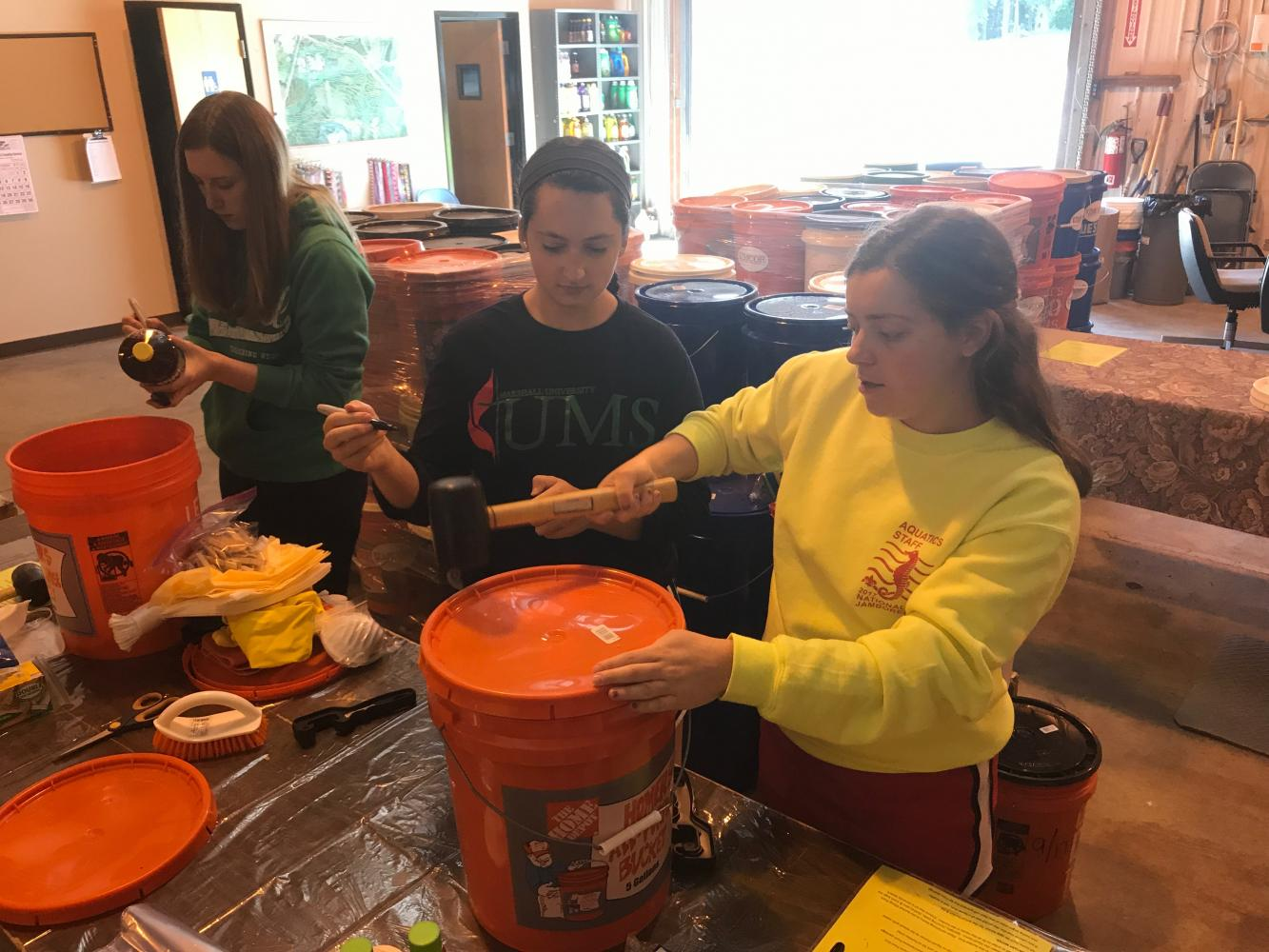 United Methodist Students members and Marshall University sophomores (from left to right) Kayleigh Terrel, Jennifer Gerst and Betsy Horton mark up items and hammer down lids on flood buckets to be sent to survivors of Harvey and Irma hurricanes.