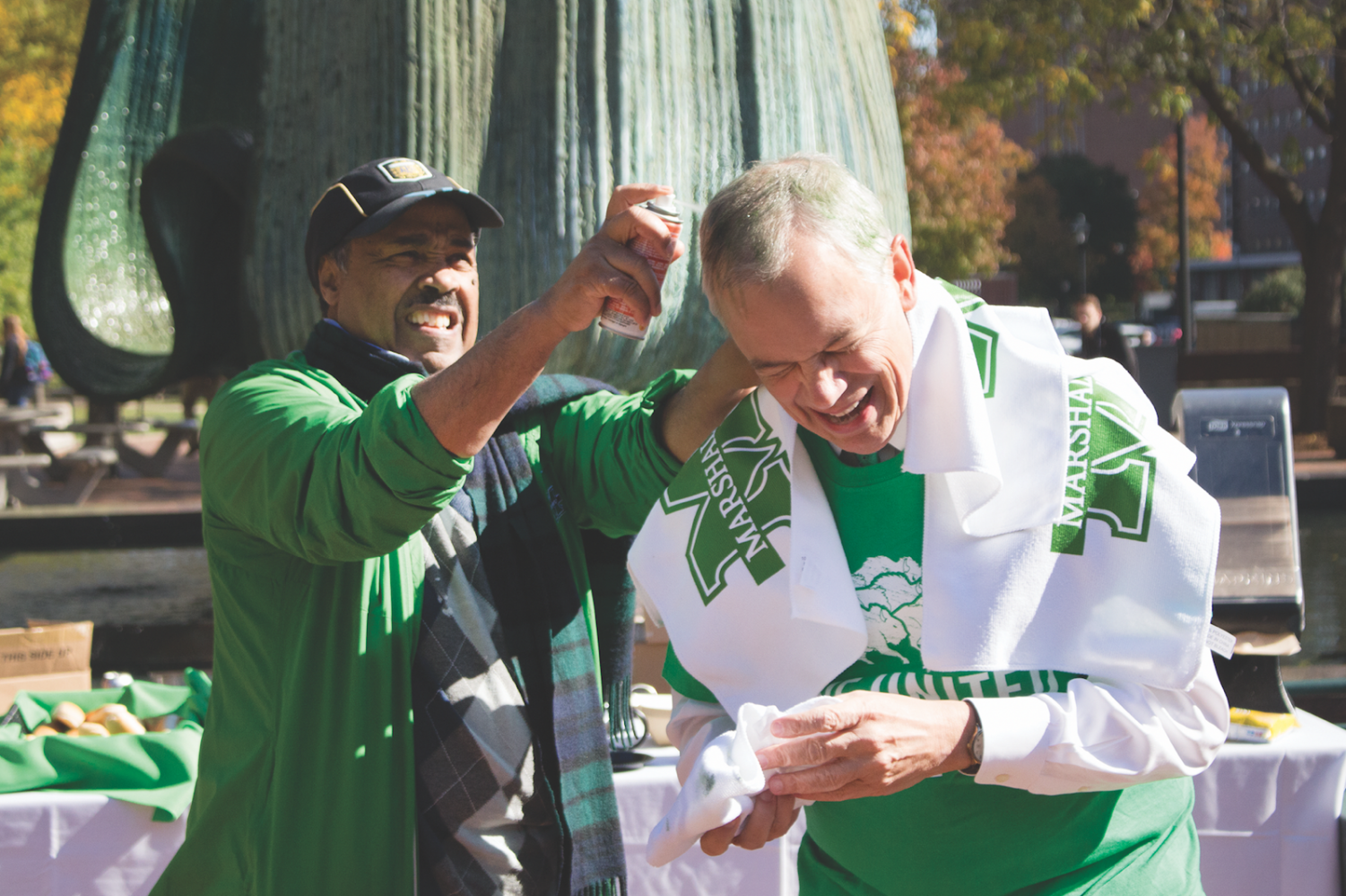 Girmay Berhie, a Marshall professor and director of the Health Informatics Department, coloring President Jerry Gilbert's hair in front of the fountain.