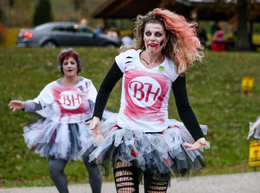 "A participant from last year's The Running Dead 5K sports a zombie outfit and zombie makeup in preparation for the race. The annual event encourages participants to dress up or simply come as ""humans."""