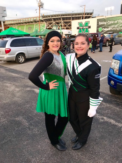 Sisters Mary and Grace Bunten stand in the parking lot of Joan C. Edwards Stadium. Mary Bunten is a senior drum major, while Grace Bunten is a freshman member of the color guard.