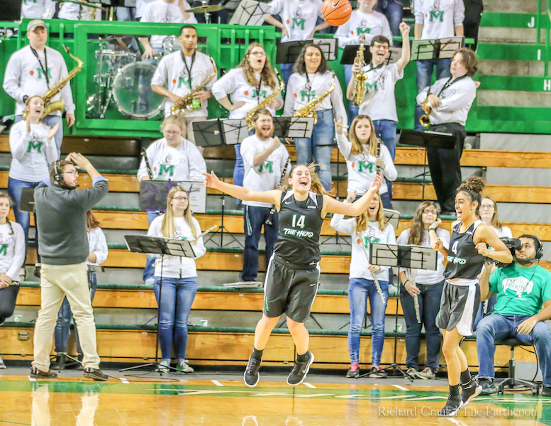 Marshall guard Shayna Gore (14) celebrates a win in front of Marshall's pep band.
